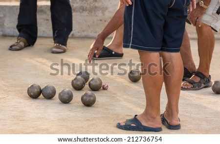 Group of senior citizens playing game of boules (petanque, bocce) on the playing field. Boules is a popular recreational activity of senior citizens in Dalmatia region of Croatia.  - stock photo