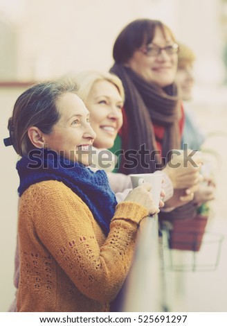 Group of senior female friends drinking tea at balcony