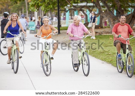 Group Of Senior Friends Having Fun On Bicycle Ride - stock photo