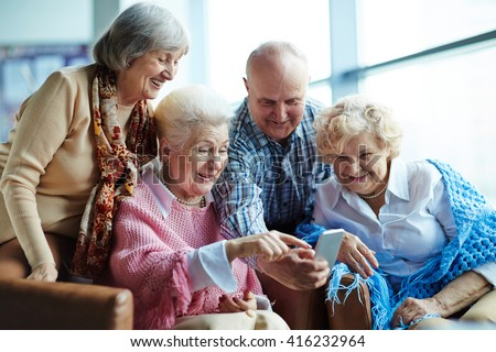 Group of senior friends watching photos on mobile phone - stock photo