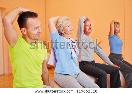 Group of senior people exercising in gym on fitness balls - stock photo