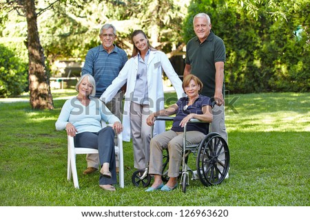 Group of senior people in retirement home garden with nurse - stock photo