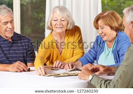 Group of senior people in retirement home playing domino game - stock photo