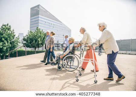 Group of senior people with some diseases walking outdoors - Mature group of friends spending their time together in a almshouse - stock photo