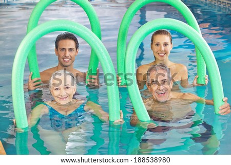 Group of senior people with swim noodles in a swimming pool - stock photo