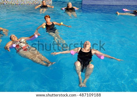 Group of senior women doing breathing exercise in outdoor swimming pool.