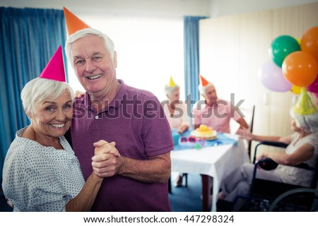 Group of seniors celebrating a birthday in the retirement house - stock photo