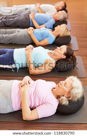Group of seniors doing relaxation exercise in gym - stock photo