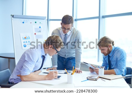 Group of serious businessmen working together at meeting - stock photo