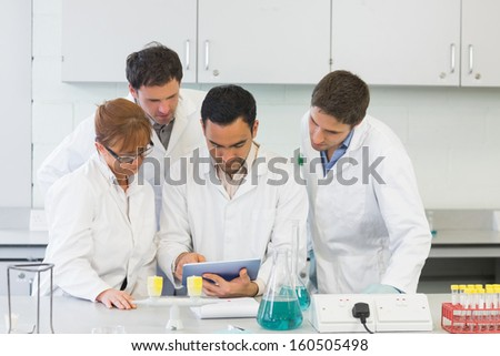 Group of serious scientists using tablet PC in the laboratory - stock photo