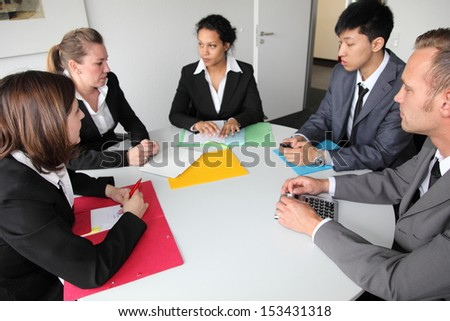 Group of serious young multiethnic business people in a meeting seated around a table discussing a problem - stock photo