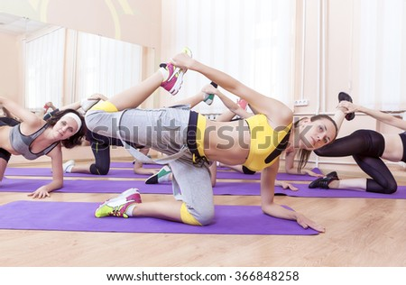 Group of Seven Caucasian Sportive Women Stretching Indoors on Sport Mats.Shot from High Point. Horizontal Image Composition - stock photo