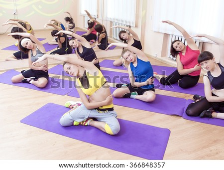 Group of Seven Caucasian Sportive Women Stretching Indoors on Sport Mats.Shot from High Point. Horizontal Image Composition