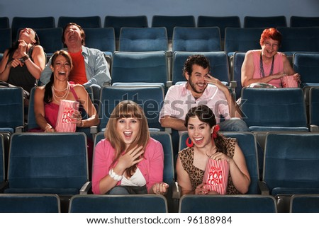 Group of seven people laughing out loud in a theater - stock photo