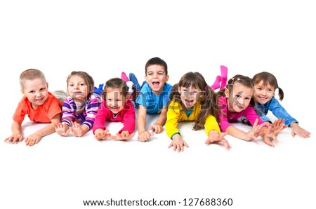 Group of seven  playful children are lying on floor  together - stock photo