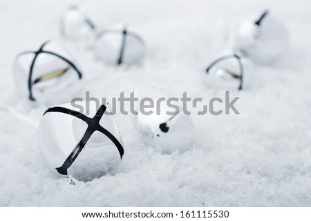 Group of several christmas bells on snow. Small shallow DOF - stock photo