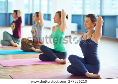 Group of several people doing yoga exercise on the floor - stock photo