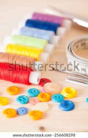 Group of sewing tools on wooden background - stock photo