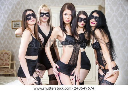 Group of sexy young woman in black lingerie, stockings and face mask in hotel room.  - stock photo