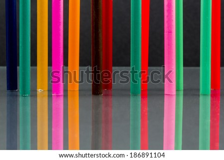 Group of sharp colored pencils with reflexions on dark background