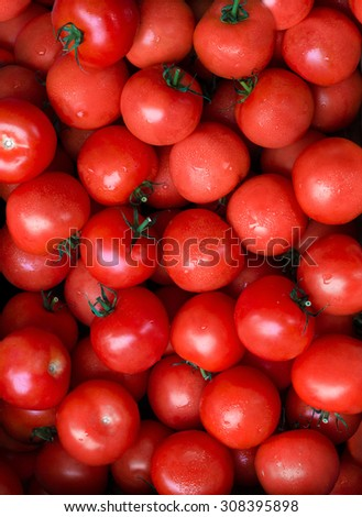 Group of shiny, red, ripe tomatoes filling the whole frame. A fresh tomato is a healthy addition to any dish due to its antioxidant properties. - stock photo