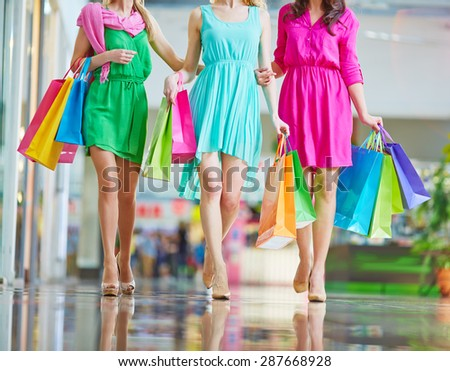 Group of shoppers in bright dresses carrying paperbags - stock photo