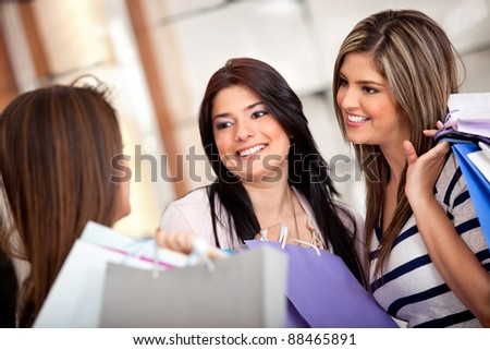 Group of shopping women talking at a store and holding with bags