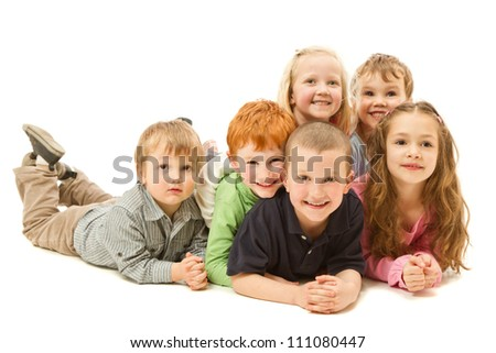 Group of six children laying down on other kids on floor together. Isolated on white.