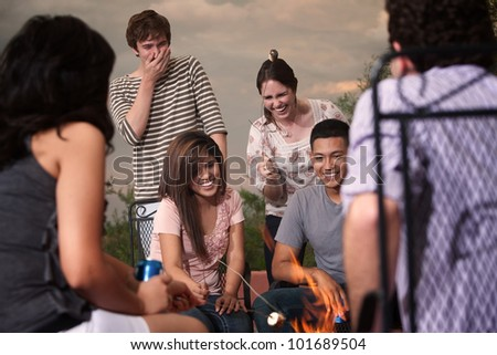 Group of six friends roasting marshmallows in a cookout party
