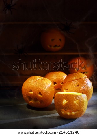 Group of Six Jack o Lanterns Carved from Oranges with Shelves in Background - stock photo