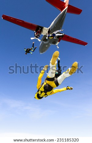 Group of skydivers jumping out of an airplane.