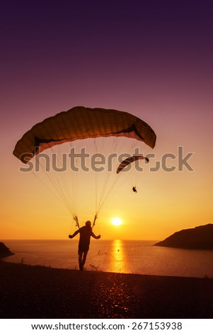 Group of skydivers ready to start flying on background of sunset sky and sea - stock photo