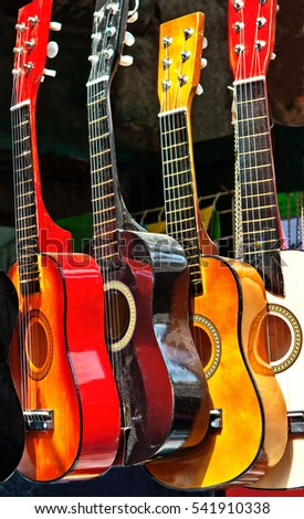 Group of small bright decorative colorful guitars for sale. Useful for background.