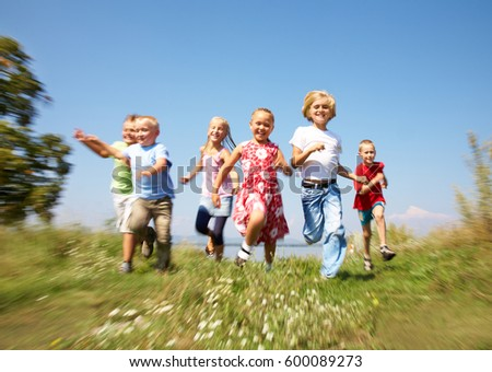 Group of small children running happily on the green meadow