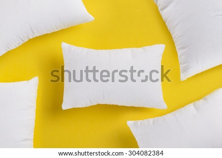 Group of small white pillows on yellow background. Need to rest and sleep - stock photo