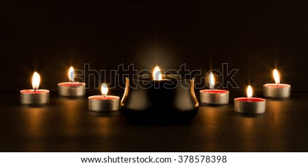Group of smaller glowing candles with a bigger burning candle in front on black background