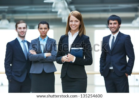 Group of smart businesspeople with happy female leader in front - stock photo
