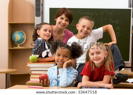 Group of smart schoolkids and their teacher looking at camera in classroom - stock photo
