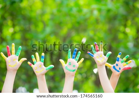 Group of smiley hands against green spring background - stock photo