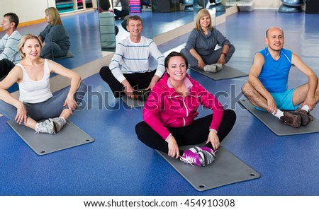 Group of smiling active adults doing pilates routine in a sport club - stock photo