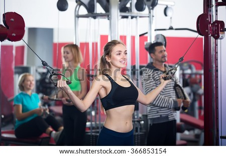 Group of smiling active women and man doing powerlifting on machines in fitness club  - stock photo