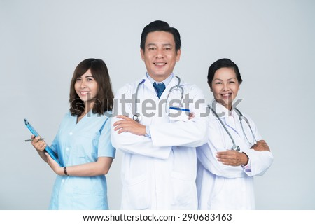 Group of smiling Asian medical workers with leader in front