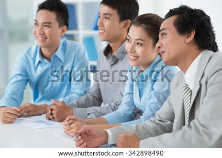 Group of smiling business people listening to presentation in the office - stock photo