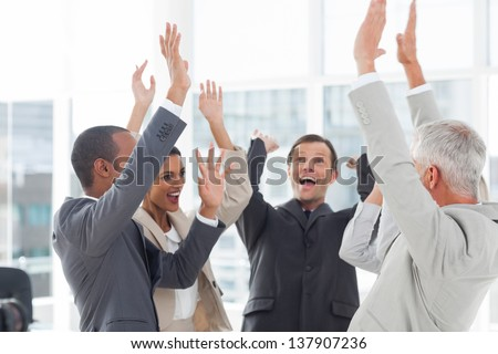 Group of smiling business people raising their hands in the workplace