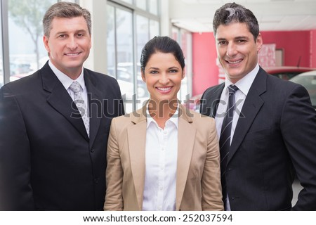 Group of smiling business team standing together at new car showroom - stock photo