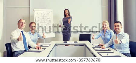 group of smiling businesspeople showing thumbs up - stock photo
