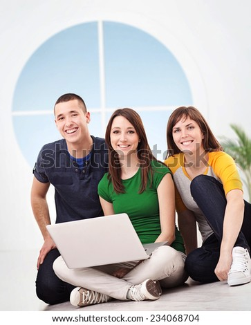 Group of smiling Caucasian people using a laptop together. - stock photo