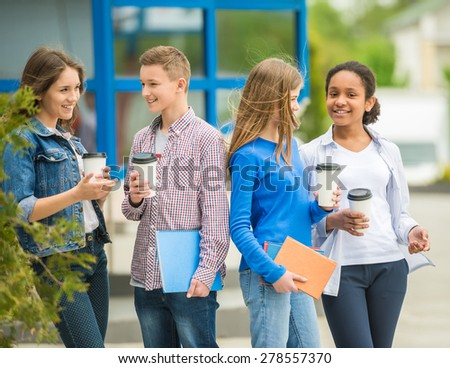 Group of smiling cheerful teenagers drinking coffee at park after lessons. - stock photo