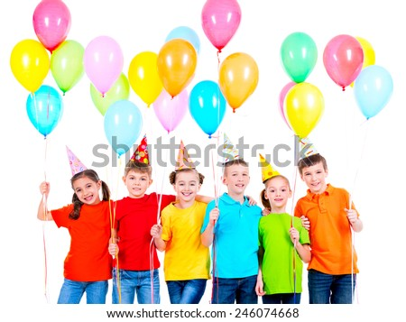 Group of smiling children in colored t-shirts and party hats with balloons on a white background. - stock photo