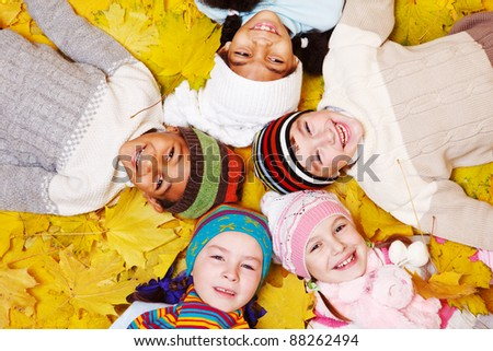 Group of smiling children on autumnal leaves